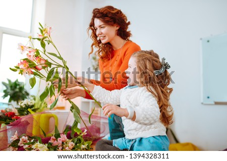 Cheerful daughter. Cheerful daughter with wavy hair having fun while looking at flowers with mom #1394328311