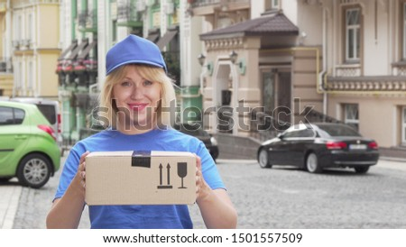 Cheerful delivery woman in blue uniform holding cardboard box. Friendly female courier working in delivery service, holding out parcel to the camera. Online consumerism concept