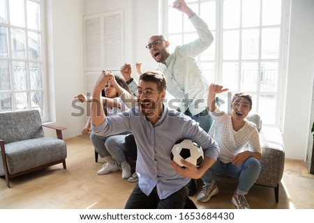 Cheerful diverse best friends watching together football worlds championship in living-room, caucasian excited fellow holds soccer ball supporting favourite sport team, mates screaming celebrating win