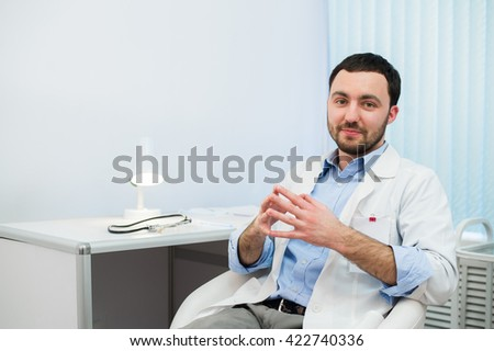 Cheerful doctor talking and looking into the camera. Doctor talking with the patient while sitting at a table in the hospital.