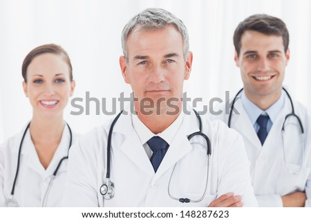 Cheerful doctors posing together crossing arms in bright office