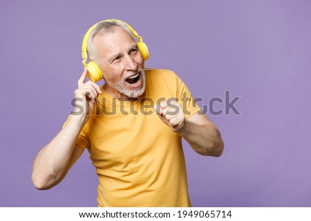 Cheerful elderly gray-haired mustache bearded man in casual yellow t-shirt posing isolated on violet wall background studio portrait. People lifestyle concept. Listen music with headphones, sing song