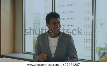Cheerful elegant African-American man in suit with pen smiling while communicating with coworkers in office