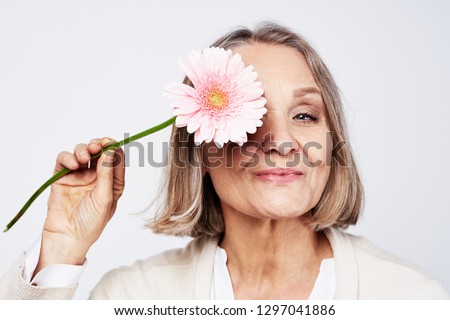 Cheerful elegant elderly woman holding a flower near the face on a gray background