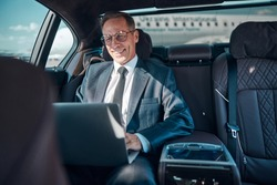 Cheerful elegant man in glasses is sitting in car with notebook while being transfered at airport