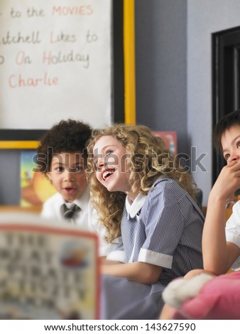 Cheerful elementary schoolgirl with boys sitting in classroom