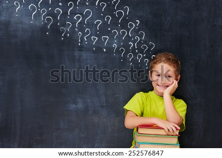 Cheerful encoureged primary school age boy have a lot of question after reading a pile of books