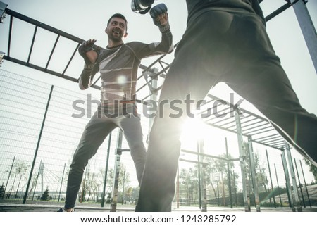 Cheerful enthusiastic MMA boxer wearing boxing gloves and smiling while looking at his friend during the training