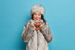 Cheerful eskimo woman shapes heart gesture expresses love dressed in warm winter clothing isolated over blue background. Affectionate reindeer herder in fur outerwear. Nothern people and cold season