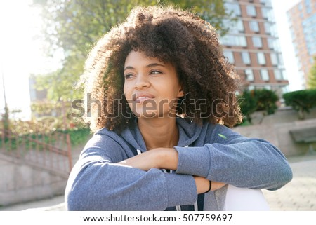 Cheerful ethnic girl relaxing in street