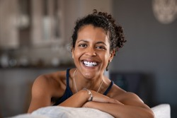 Cheerful ethnic mid adult woman relaxing on sofa at home. Successful young african woman with toothy smile sitting on couch and looking at camera. Portrait of confident black woman laughing.