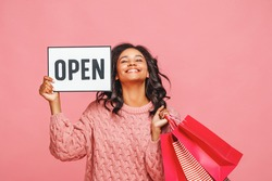 Cheerful ethnic woman with paper bags smiling and looking at camera while showing signboard with Open inscription during shopping against pink background