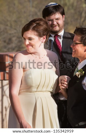 Cheerful European woman with bride and rabbi outdoors