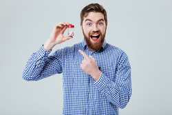 Cheerful excited bearded young man standing and pointing on bottle of pills