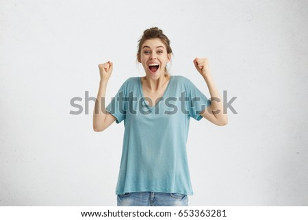 Cheerful excited European female screaming in delight and excitement, clenching fists after being promoted. Happy supportive young mother cheering for her son during football match, isolated on white #653363281