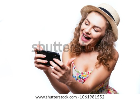 Cheerful excited girl in cap play games or make video call on smartphone on white background #1061981552