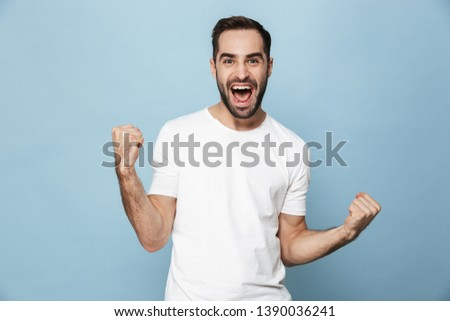 Cheerful excited man wearing blank t-shirt standing isolated over blue background, celebrating success Foto stock ©