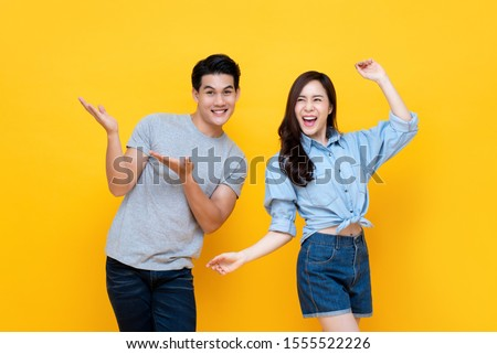 Cheerful excited young Asian man and woman smiling and dancing isolated on yellow background