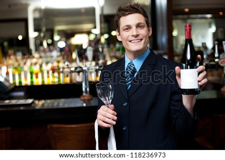 Cheerful executive posing with a bottle of wine. Bar in the background #118236973