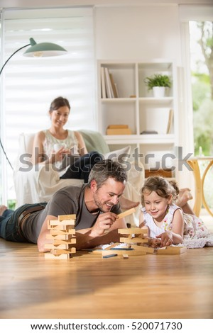 Cheerful family at home, Daddy and his young daughter lying on the wooden floor are playing with a wooden game.  At background mom is sitting in an armchair while using a digital tablet