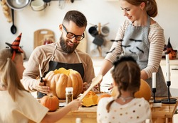 Cheerful family bearded father making jack o lantern from pumpkin while gathering around table with mother and children in cozy kitchen during Halloween celebration at home