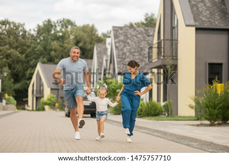 Cheerful family. Cheerful parents and daughter running while spending time outside in the evening #1475757710
