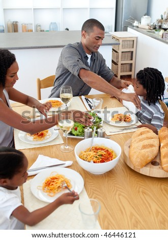 Cheerful family dining together in the kitchen