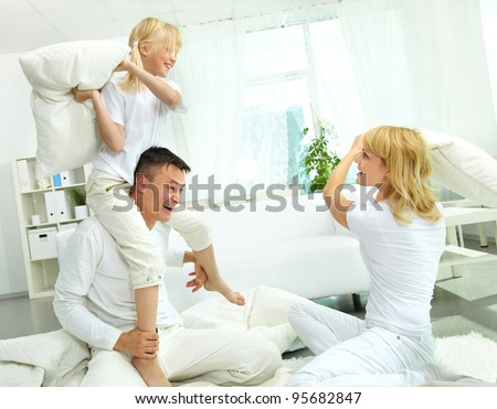 Cheerful family having a lot of fun fighting pillows