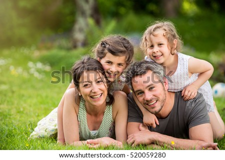 Cheerful family in a park, Dad, mum and heir two lovely daughter are lying on the grass while they are looking at camera. Shot with flare