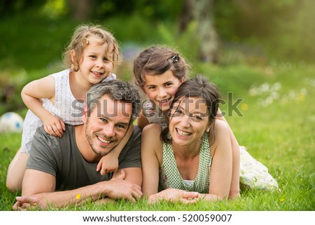 Cheerful family in a park, parents and their two lovely daughter are lying on the grass while they are looking at camera. Shot with flare