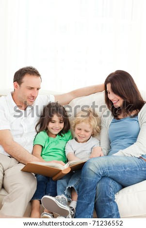Cheerful family looking at a photo album together on the sofa