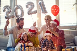 Cheerful family looking forward New Year presents in festive home atmosphere. New Year, holiday, family time together