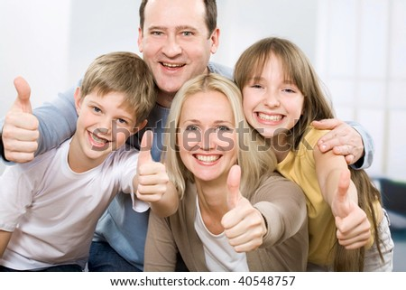 Cheerful family of four with their thumbs up