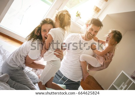 Cheerful family playing together on bed. Parents spending free time with their daughters. Little girl sitting on fathers hand.