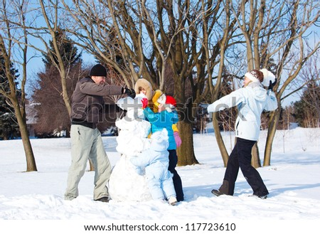 Cheerful family playing with snow