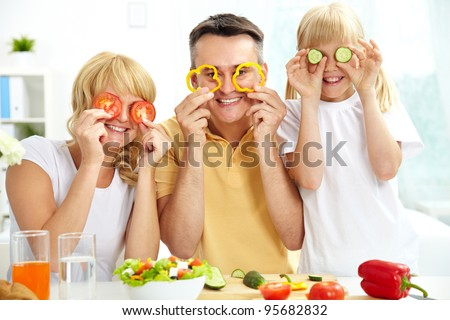 Cheerful family playing with vegetables in kitchen, healthy food