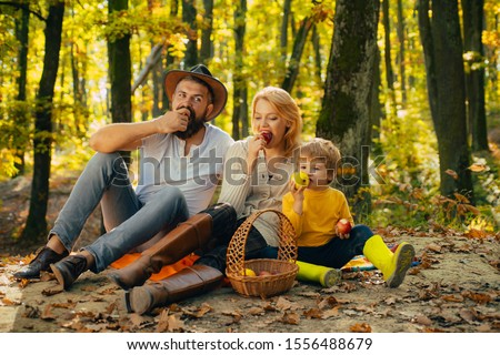 Cheerful family sitting on the grass during a picnic in a park. Mom, dad and baby happy relax at sunset. There is a basket with meal and toys for the kid. Autumnal family walk concept