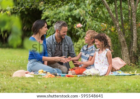 Cheerful family sitting on the grass during a picnic in a park, there is a basket with meal and toys for the kids