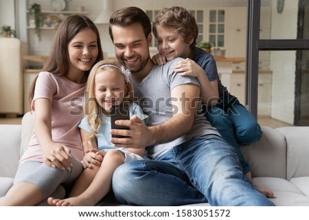 Cheerful family with little kids seated on sofa play new game on smartphone, take selfie photo having fun on-line using app, make video call talk with relatives, buying distantly e-commerce concept