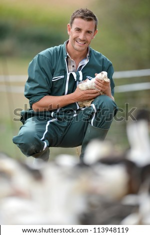 Cheerful farmer holding duck in his arms