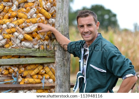 Cheerful farmer standing by corn silo