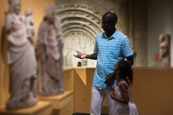 Cheerful father and daughter standing at hall of museum and looking at exhibits of medieval sculpture