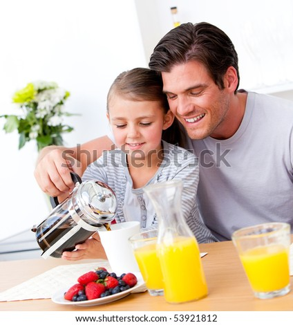 Cheerful father and his daughter having breakfast together in the kitchen