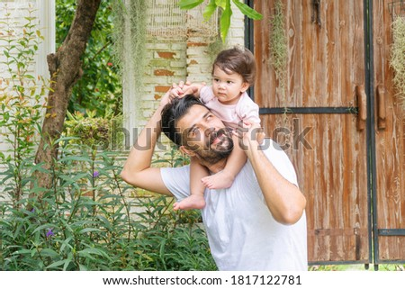 Cheerful father holding and piggyback his baby daughter in his neck while relax time at home. Enjoyment little lovely mixed race girl over daddy shoulder in the garden . Happy fathers day concept. stock photo