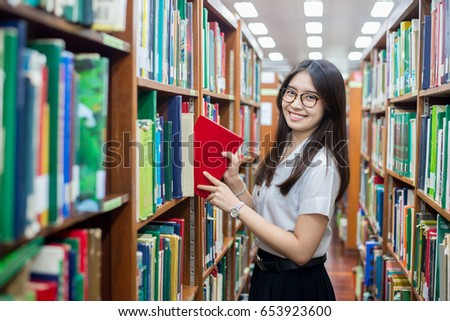 Cheerful female Asian student putting in order books returned after reading for literature lesson standing near bookshelves in modern interior library of university during break between lesson.