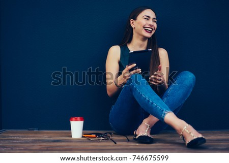 Cheerful female blogger dressed in trendy outfit having fun during online chatting with friends in social network.Emotional hipster girl loudly laughing while sitting next to wall with copy space
