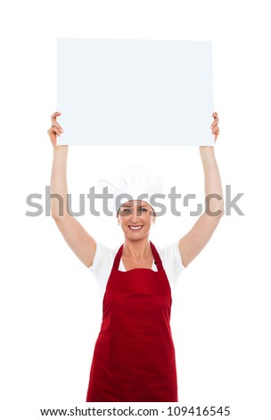 Cheerful female chef holding blank advertising board over her head in front of camera