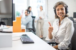Cheerful female customer service operator showing thumbs up in office.
