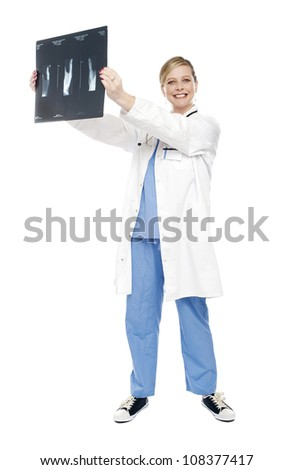 Cheerful female doctor holding x-ray report and analyzing same. Full length shot