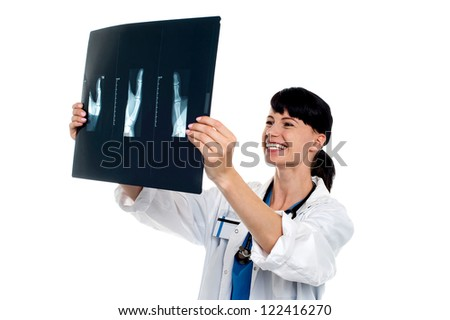 Cheerful female doctor reviewing patients x-ray report. Isolated on white background.